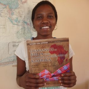 'Please ask God to help me to lead his people in a true way.' Happiness Mbumi graduates from Msalato Theological College with a Swahili edition of the Africa Bible Commentary.